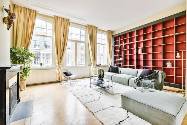Salon oświetlony słońcem z dużymi oknami i szarą kanapą z dywanem na tle czerwonych półek z książkami