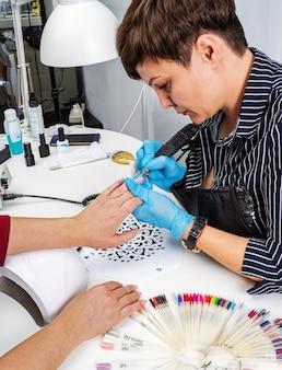 Salon paznokci, ręce klienta i mistrza z bliska. leczenie paznokci frezem