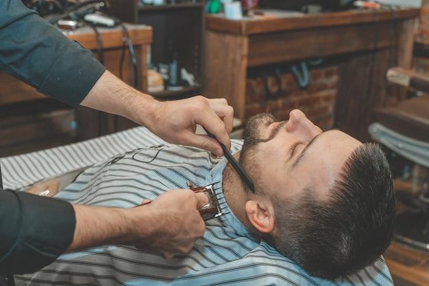 Salon piękności dla mężczyzn. golenie brody w zakładzie fryzjerskim. fryzjer przycina brodę brzytwą i maszynką do strzyżenia. bliska brutalne fryzury. sprzęt fryzjerski. selektywne ustawianie ostrości.
