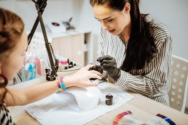 Salon piękności. nastoletnia dziewczyna na sobie jasne bransoletki przychodzących do salonu piękności i po manicure