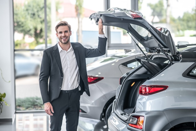 Salon samochodowy. młody dorosły uśmiechnięty atrakcyjny mężczyzna w ciemnym garniturze stojący w pobliżu otwartego bagażnika samochodu w salonie w ciągu dnia