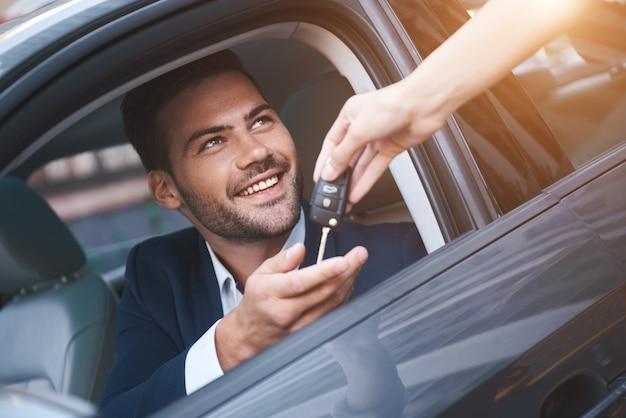 Salon samochodowymłody mężczyzna otrzymujący kluczyk do samochodu od sprzedawczyni