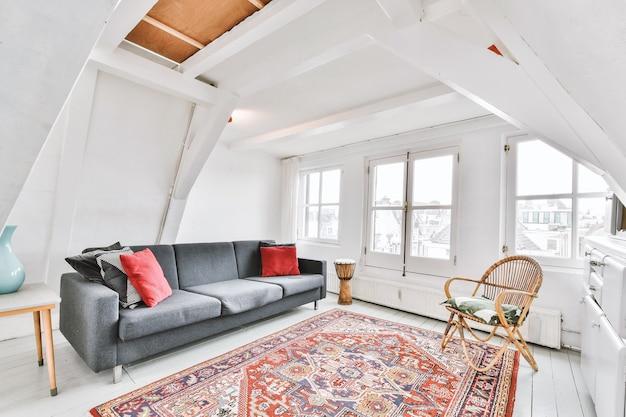 Salon w kolorze białym z orientalnym dywanikiem wyposażony w szarą sofę i rattanowy fotel