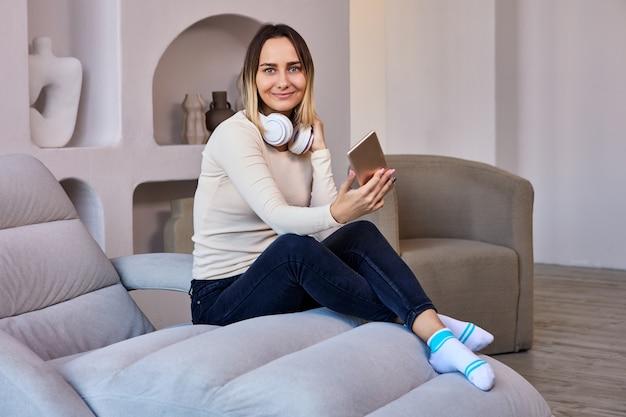 Salon, w którym kobieta na kanapie i słuchawkach trzyma telefon