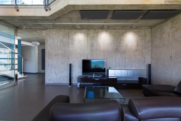 Salon we wnętrzu nowoczesnego domu betonowego.