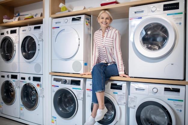 Salon wystawowy. blondynka w pasiastej koszuli siedzi na pralce