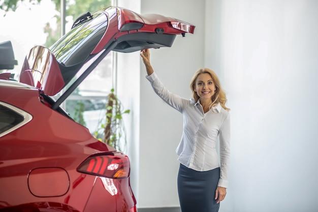 Salon wystawowy. ładna blondynka kobieta stojąca nea czerwony samochód