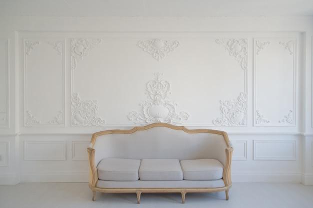 Salon z antyczną stylową lekką sofą na luksusowej białej płaskorzeźbie z płaskorzeźbami sztukaterie rokokowe elementy