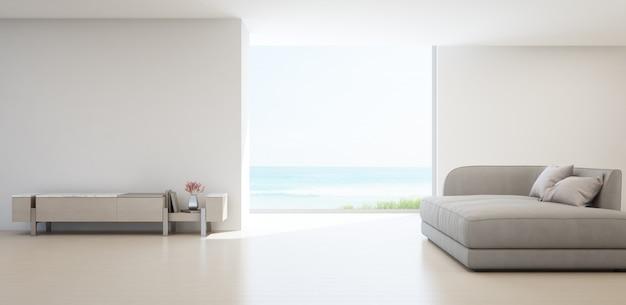 Salon z widokiem na morze luksusowego letniego domu na plaży ze stojakiem na telewizor i drewnianą szafką.