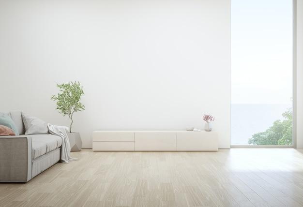 Salon z widokiem na morze luksusowego letniego domu na plaży ze stolikiem telewizyjnym i drewnianą szafką.