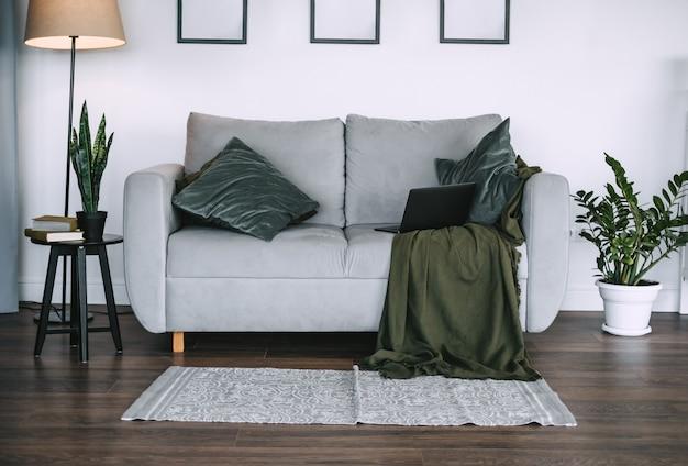 Salon z zielonymi roślinami i szarą sofą z poduszką i laptopem.