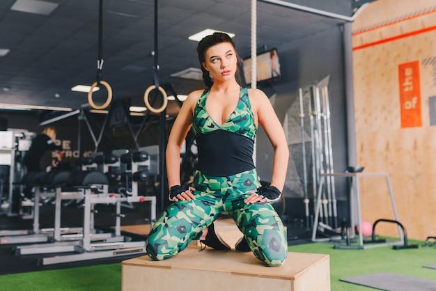 Salowy strzał dysponowana młoda kobieta bierze przerwę od jej treningu przy gym. instruktor fitness relaksujący na siłowni crossfit.