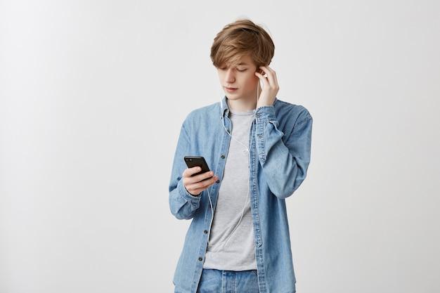 Salowy strzał młody caucasian mężczyzna z jasnym włosy ubierał w drelichowej koszula odpoczywa po zajęć na uniwersytecie. facet słucha muzyki w białych słuchawkach, używając aplikacji muzycznej na smartfonie.