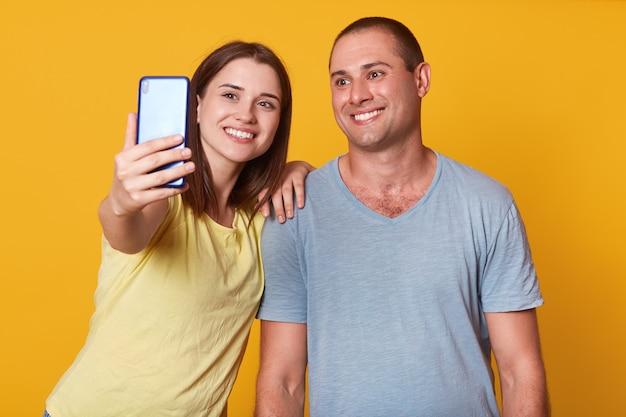 Salowy strzał piękna młoda para patrzeje kamerę telefon komórkowy, robi selfie portretowi, będący ubranym popielate i żółte koszulki