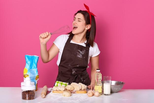Salowy studio strzał śmieszna śpiewacka brunetka przy kuchnią