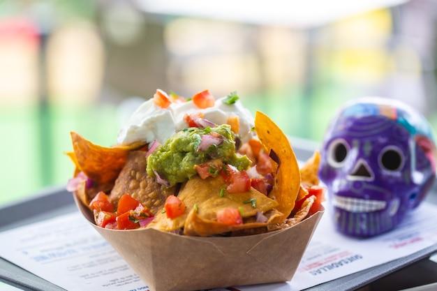 Salsa nachos na papierowym talerzu w ulicznej kawiarni z figurką niebieskiej czaszki