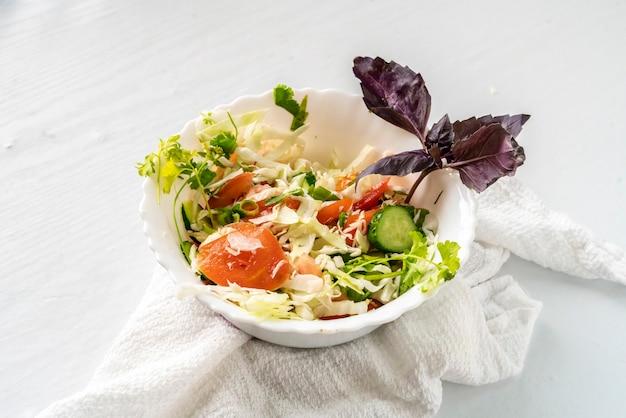 Salsad detox w białej ceramicznej misce z kapustą, pomidorami i bazylią na białym tle