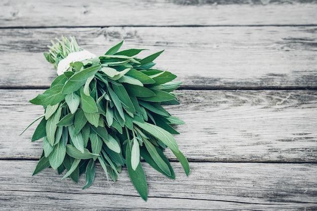 Salvia officinalis. szałwia pozostawia na starym drewnianym stole. skopiuj miejsce.