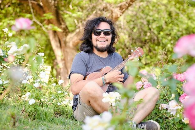 Sam latynos grający na ukulele, siedzący na środku łąki pełnej kwiatów, w słoneczny wiosenny dzień.
