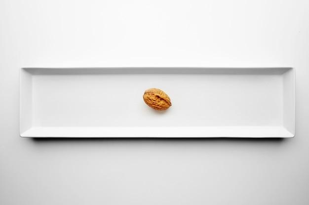Sam orzech włoski samodzielnie w środku prostokątnej płytki ceramicznej na białym stole