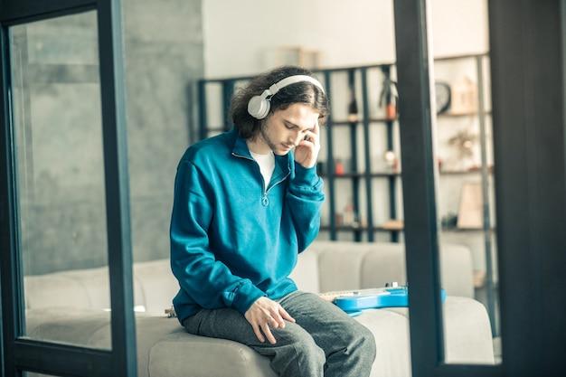 Sam w domu. przystojny melancholijny facet spędzający spokojny dzień w domu słuchając muzyki w słuchawkach
