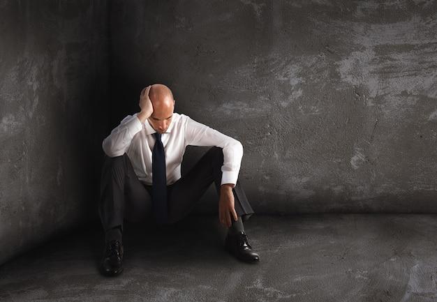 Sam zdesperowany biznesmen siedzi na podłodze. pojęcie samotności i porażki