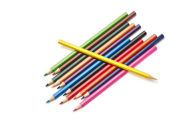Sam żółty ołówek leży na stosie innych kolorowych ołówków