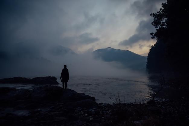 Sama sylwetka człowieka w białej mgiełce na tle gór i rzeki. gęsta mgła o wieczornym zmierzchu. tajemnicza atmosfera. refleksja, medytacja.
