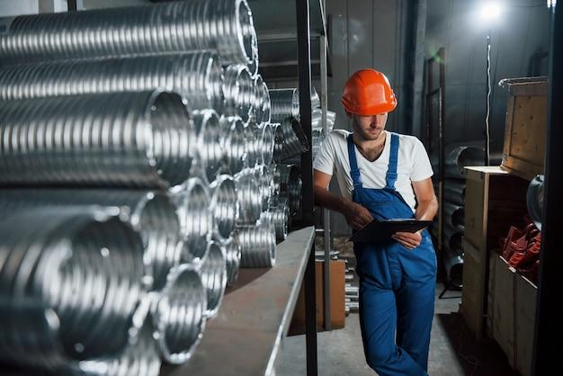 Sama w magazynie. mężczyzna w mundurze pracuje nad produkcją. nowoczesna technologia przemysłowa.