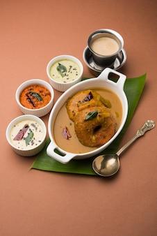 Sambar vada lub medu vada, popularne południowoindyjskie jedzenie podawane z zielonym, czerwonym i kokosowym chutneyem na nastrojowym tle. selektywne skupienie