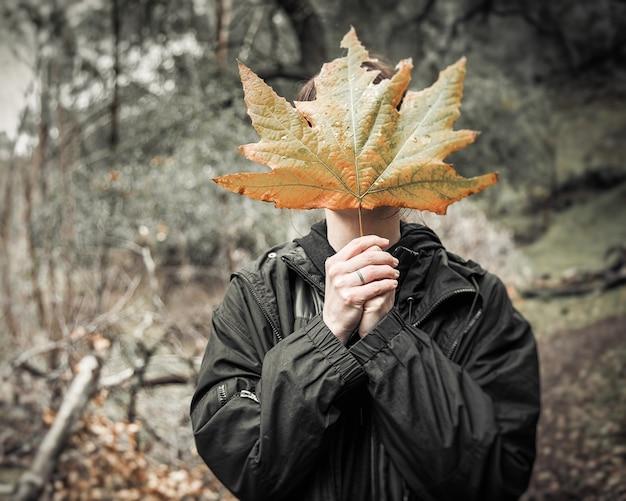 Samica zasłaniająca twarz dużym jesiennym liściem stojąca w środku lasu