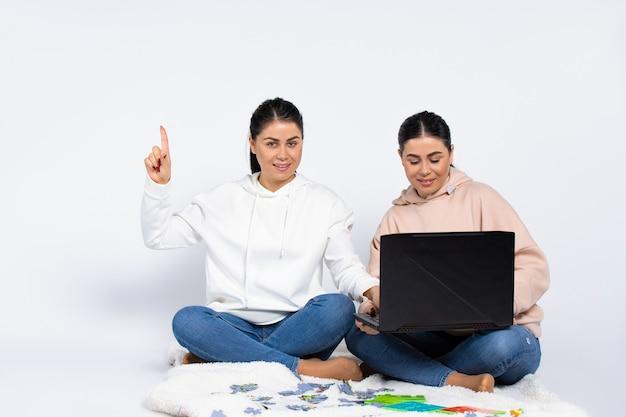 Samice bliźniaczki mają idealne spojrzenie na aparat na białym tle na białym tle laptop i siostry puzzli spędzają czas