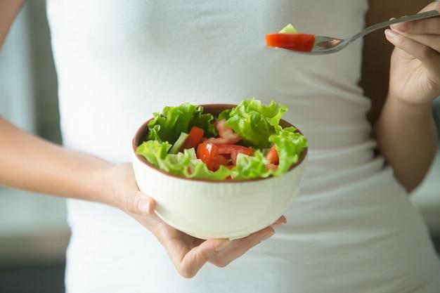 Samice dłonie trzyma miskę zielonej sałatki