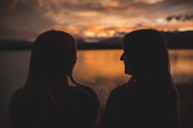 Samice siedzą na brzegu podczas zachodu słońca nad jeziorem polka w nowej zelandii