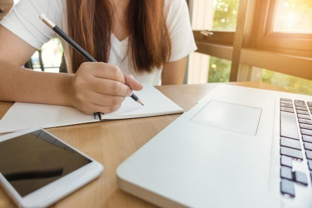 Samice studenta notatek z książki w bibliotece. młoda kobieta azjatyckich siedzi w tabeli robi zadania w bibliotece kolegium. obrazy stylu efektów klasycznych.