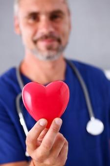 Samiec doktorski jest ubranym błękita munduru chwyt w ręki czerwieni zabawki sercu