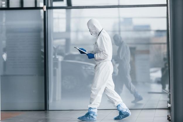 Samiec doktorski naukowiec w fartuchu, defensywnych okularach i maski mienia notepad w rękach