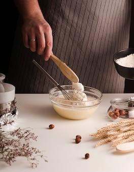 Samiec kucharz miesza składniki w pucharze