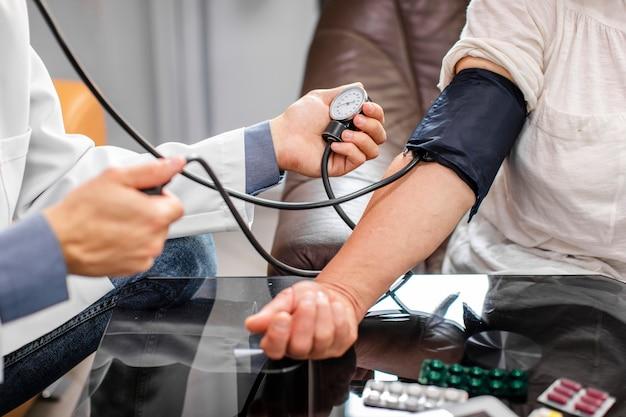 Samiec lekarka wręcza pomiarowego napięcie pacjent