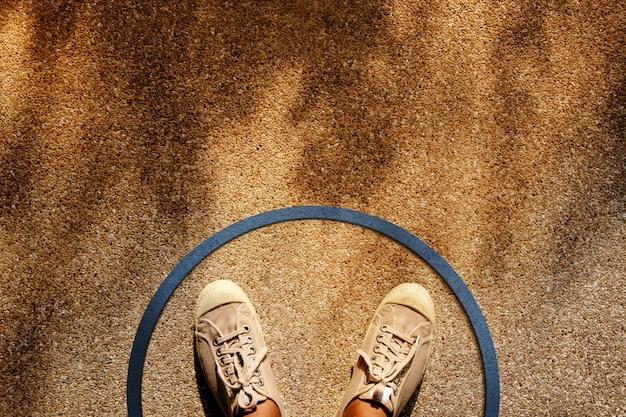 Samiec na sneaker shoes stoi wewnątrz linii circle