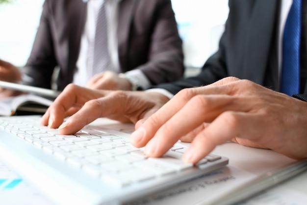 Samiec ręki w kostiumu pisać na maszynie na bielu