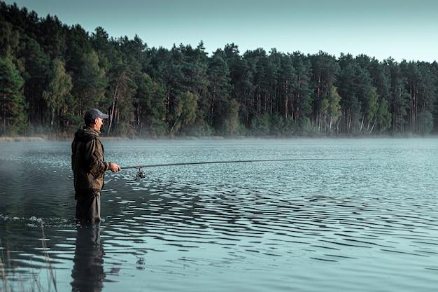 Samiec rybak na jeziorze stoi w wodzie i łowi wędkę wędkarskie wakacje hobby