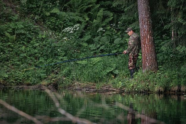Samiec rybak spokojnie łowi na brzozowym jeziorze w lesie iglastym.