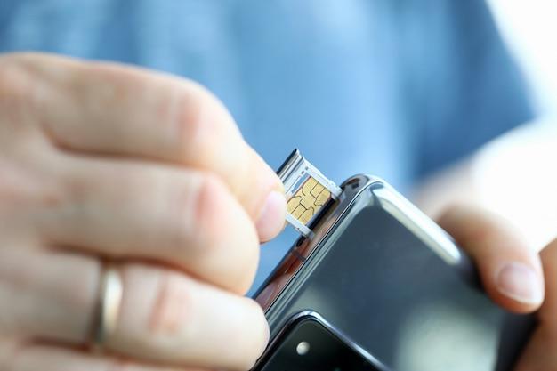 Samiec wręcza dostawać sim karty szczelinę jego smartphone out zbliżenie