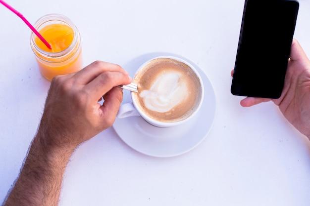 Samiec wręcza mienia smartphone z filiżanką kawy i sokiem pomarańczowym na stole. dzień, styl życia