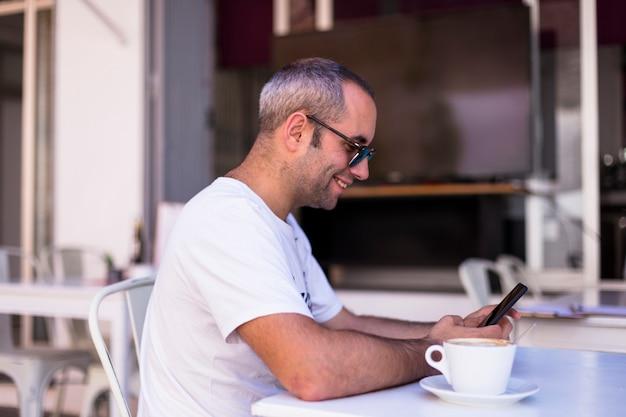 Samiec wręcza mienia smartphone z filiżanką kawy na stole w tarasie. dzień, styl życia