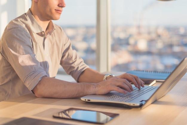 Samiec wręcza pisać na maszynie, używać laptop w biurze. projektant pracujący w miejscu pracy