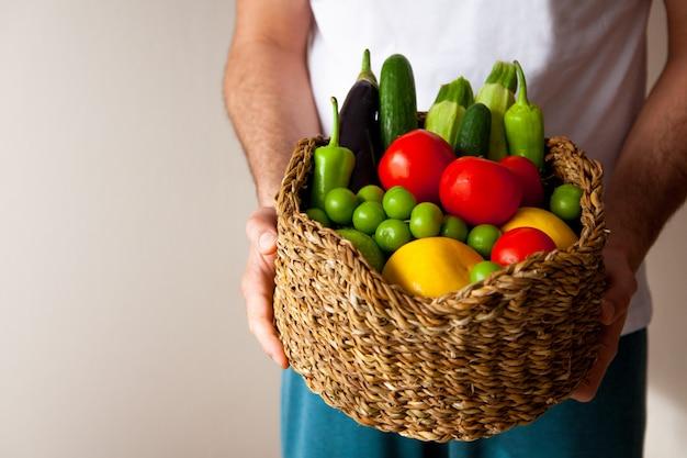 Samiec wręcza trzymać dużego kosz z różnymi świeżymi surowymi rolnymi warzywami