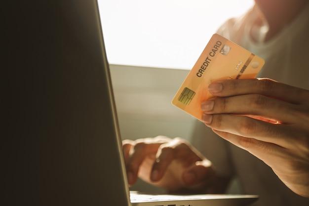 Samiec wręcza trzymać kredytową kartę i używać laptop