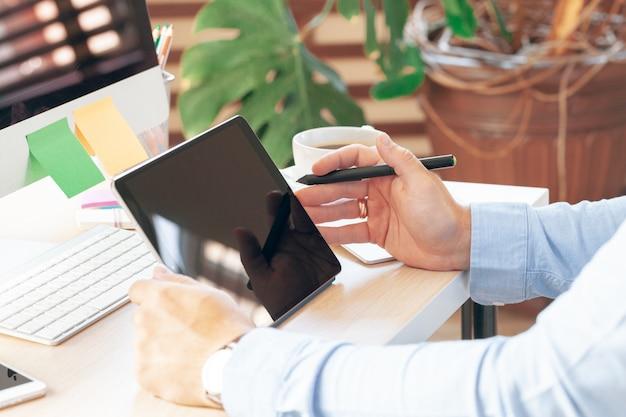 Samiec wręcza używać nowożytną cyfrową pastylkę i komputer przy biurem. nowoczesne miejsce do pracy.